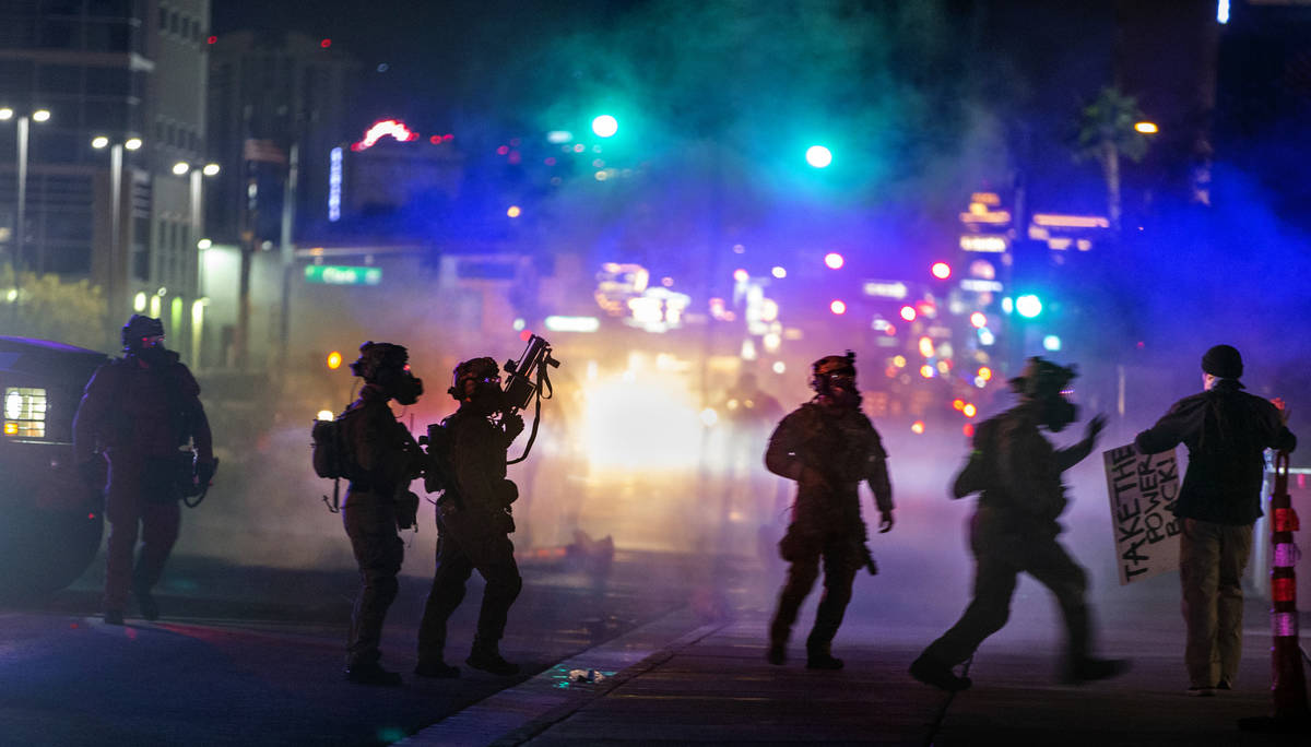 Las Vegas Police are engulfed in tear gas as they move in on a protester along Las Vegas Blvd. ...