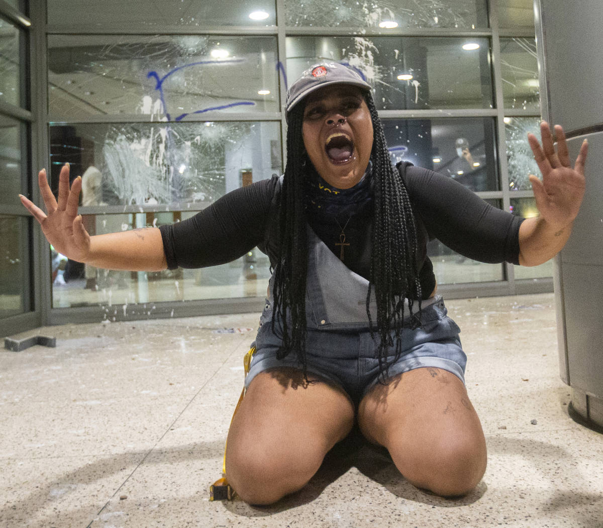 A woman pleads for protesters to stop breaking windows at an office building on South Las Vegas ...