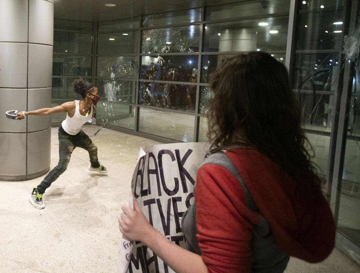 A protester throws a metal object at the window of an office building on South Las Vegas Boulev ...