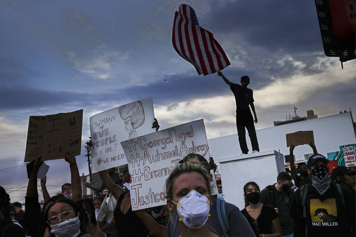 A protester waves an upside down U.S. flag the death of George Floyd in downtown Las Vegas on S ...