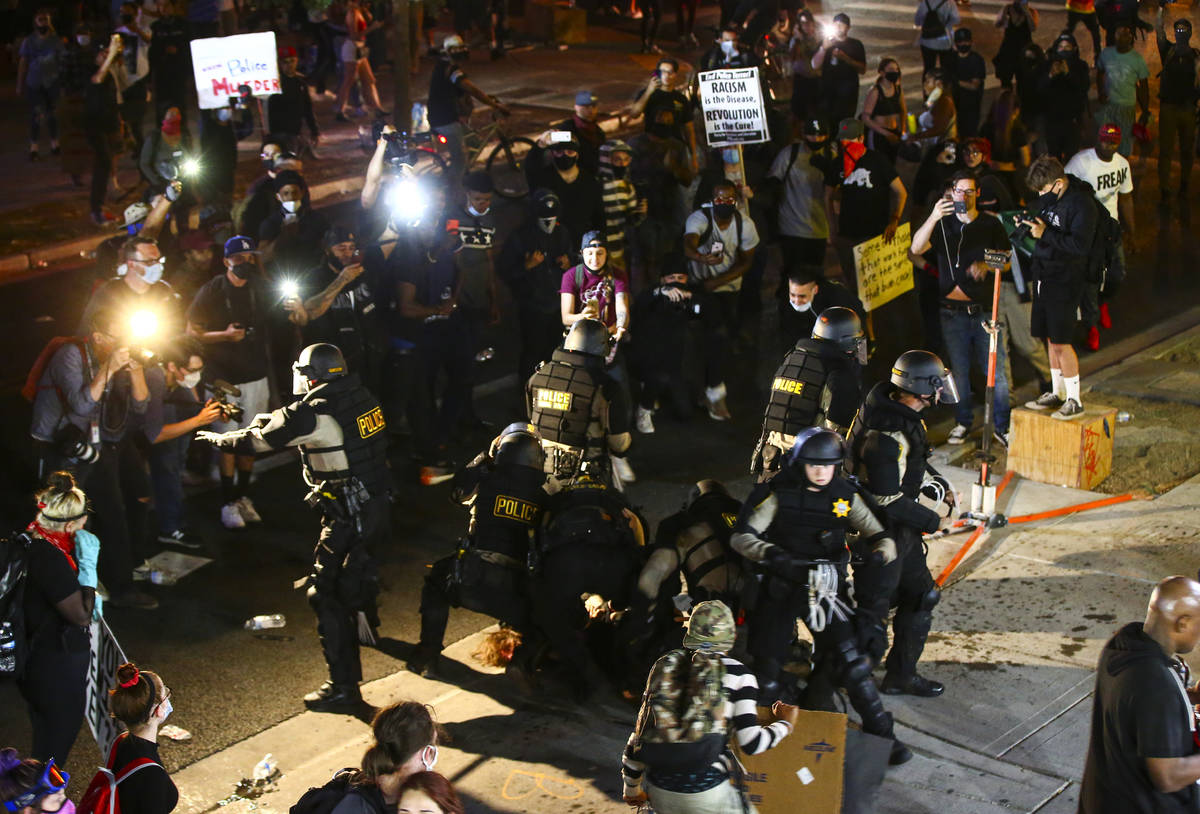 Police make an arrest as people protest the death of George Floyd in downtown Las Vegas on Satu ...