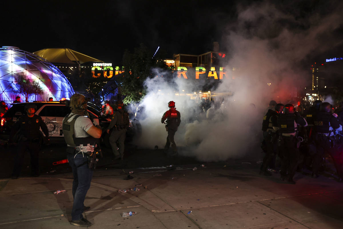 Teargas spreads around police officers as people protest the death of George Floyd in downtown ...