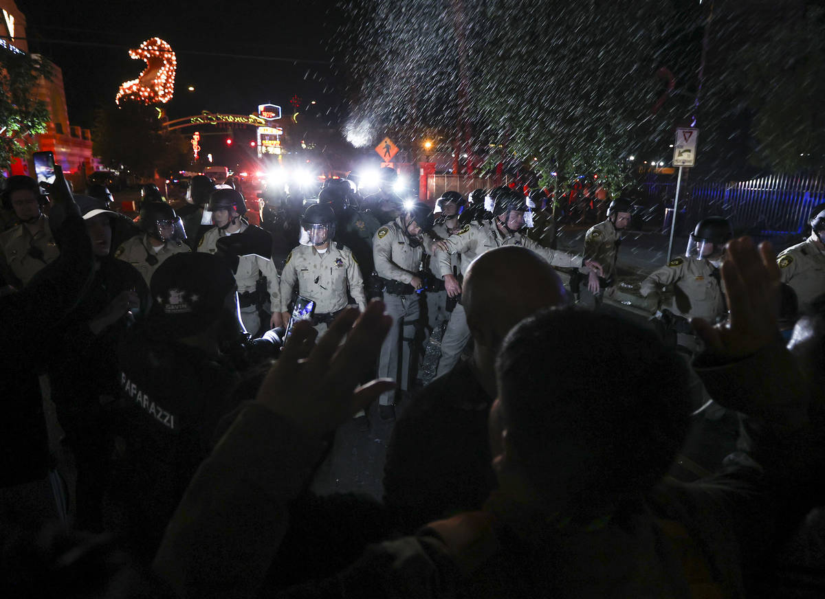 Water bottles are thrown at police officers as people protest the death of George Floyd in down ...