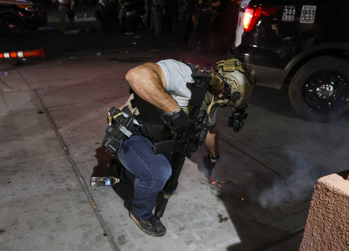 A police officer puts out a firework device that was thrown by a protester in downtown Las Vega ...