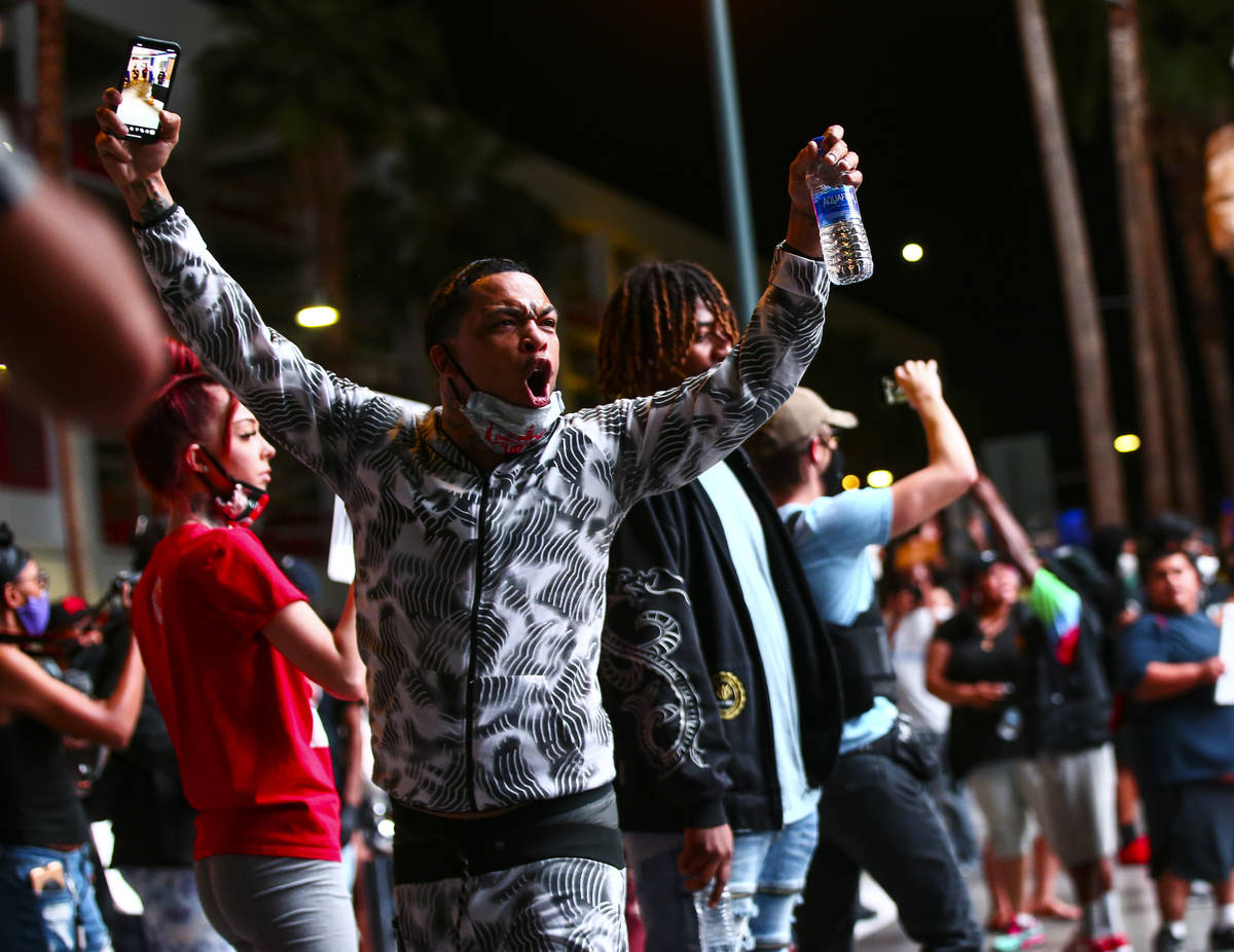 A man shouts at police while protesting the death of George Floyd in downtown Las Vegas on Satu ...
