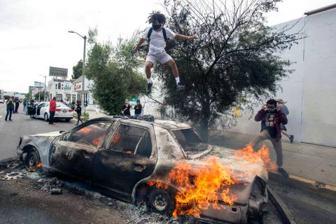A person jumps on a burning police vehicle in Los Angeles, Saturday, May 30, 2020, during a pro ...