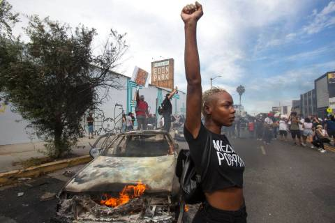 A protester poses for photos next to a burning police vehicle in Los Angeles, Saturday, May 30, ...