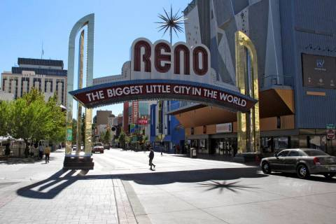 FILE - In this Oct. 11, 2016, file photo, pedestrians pass beneath the Reno arch as traffic pas ...