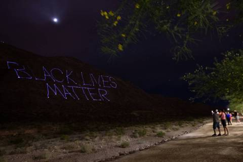 """Black Lives Matter"" is projected onto the side of Lone Mountain by the company Tag Team Produc ..."