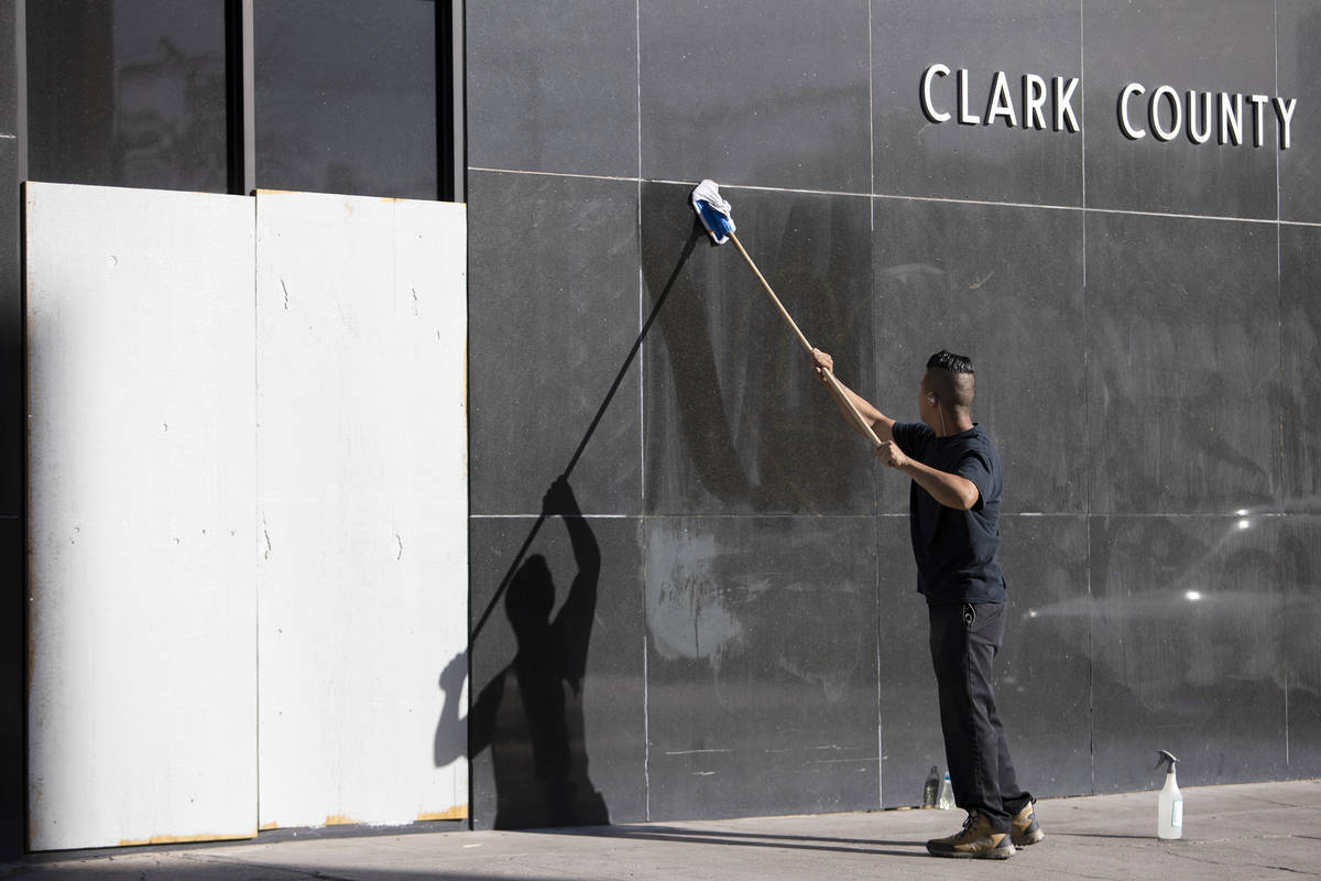 An employee from The D wipes down words written in the dirt on a Clark County building that wer ...