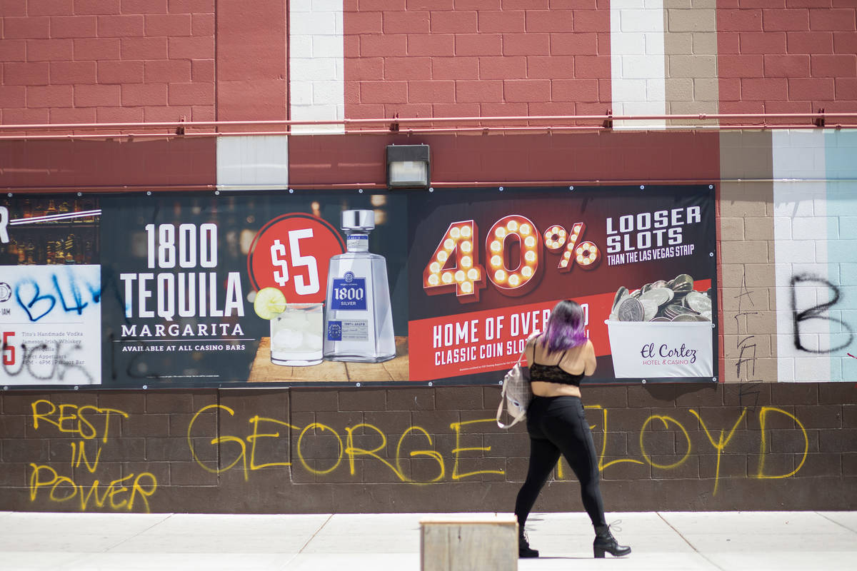 A woman photographs graffiti commemorating George Floyd, who was killed by Minneapolis police, ...