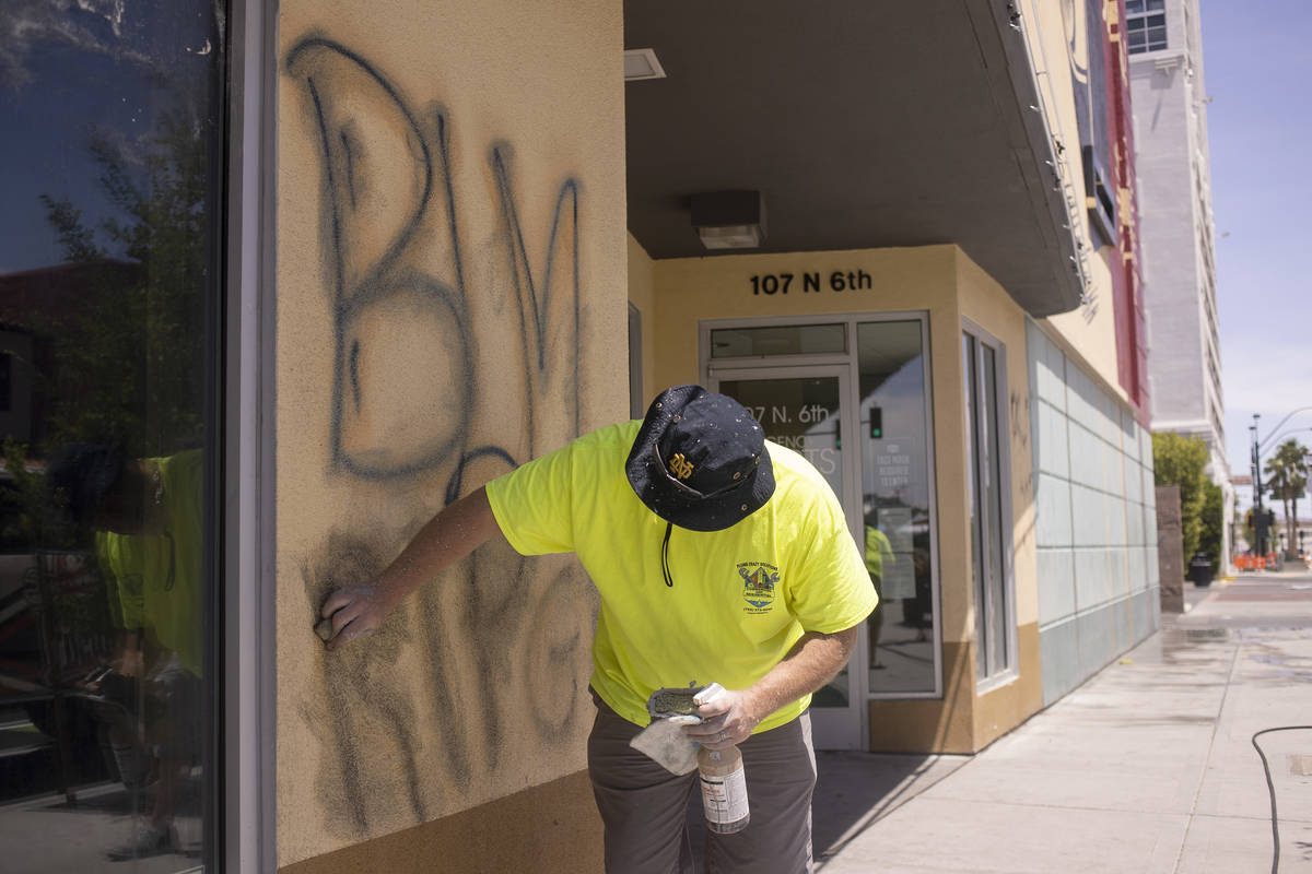 Sean Murphy cleans up graffiti at Eureka! Discover American Craft following a night of protests ...