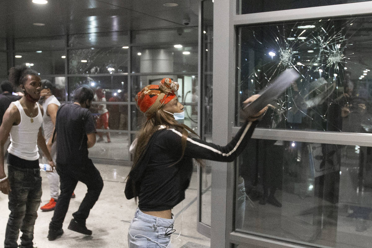 A protester smashes the window of an office building on South Las Vegas Boulevard in downtown L ...