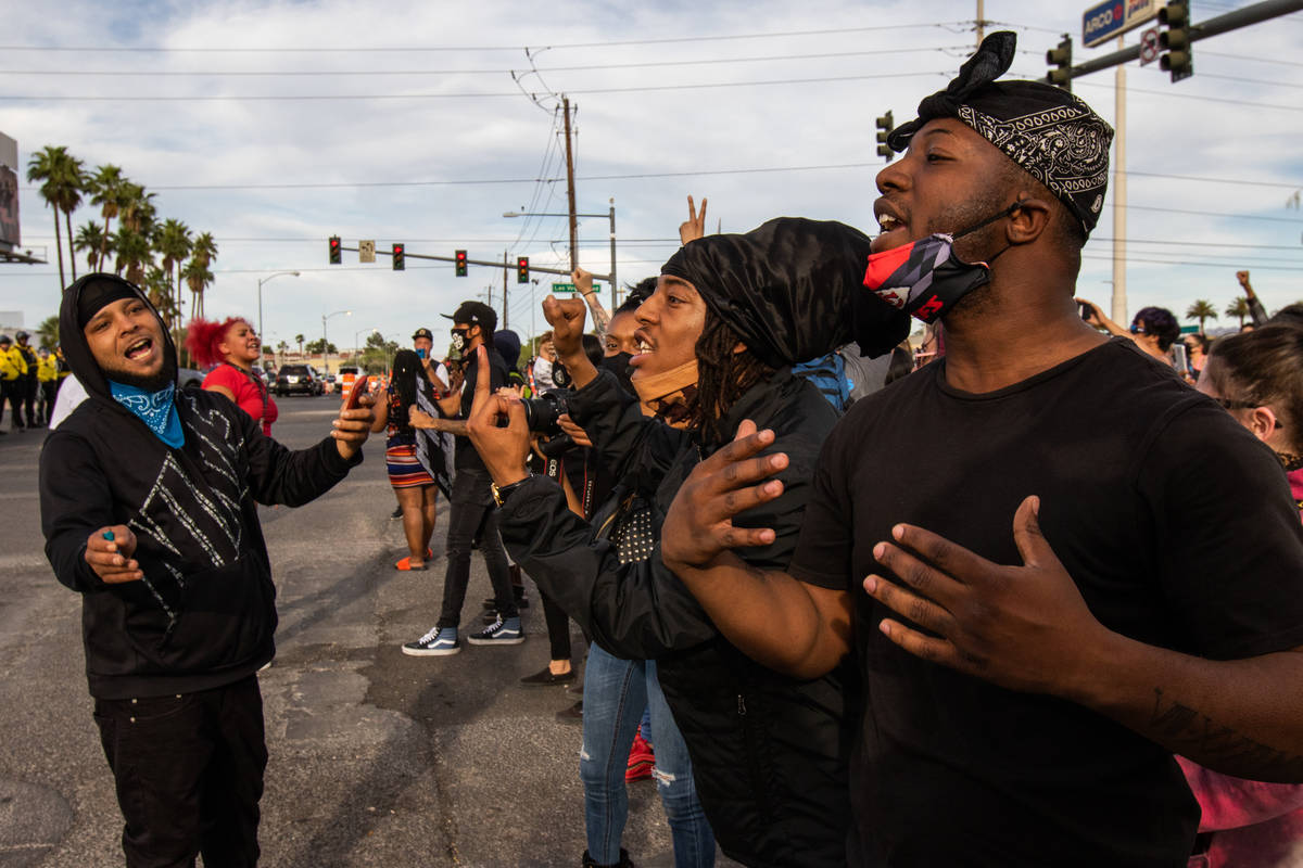 A Black Lives Matter demonstrator attempts to calm other protesters as they yell at a line of p ...