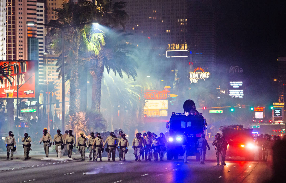 Las Vegas police officers deploy tear gas on protesters on the Strip on Sunday, May 31, 2020, i ...