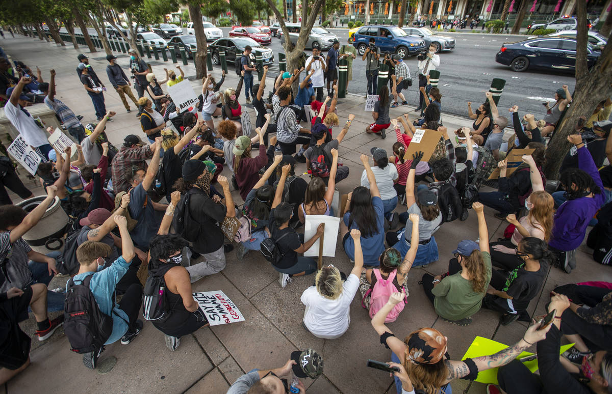 Protesters kneel and hold up fists in unity outside the Bellagio during a Black Lives Matter pr ...