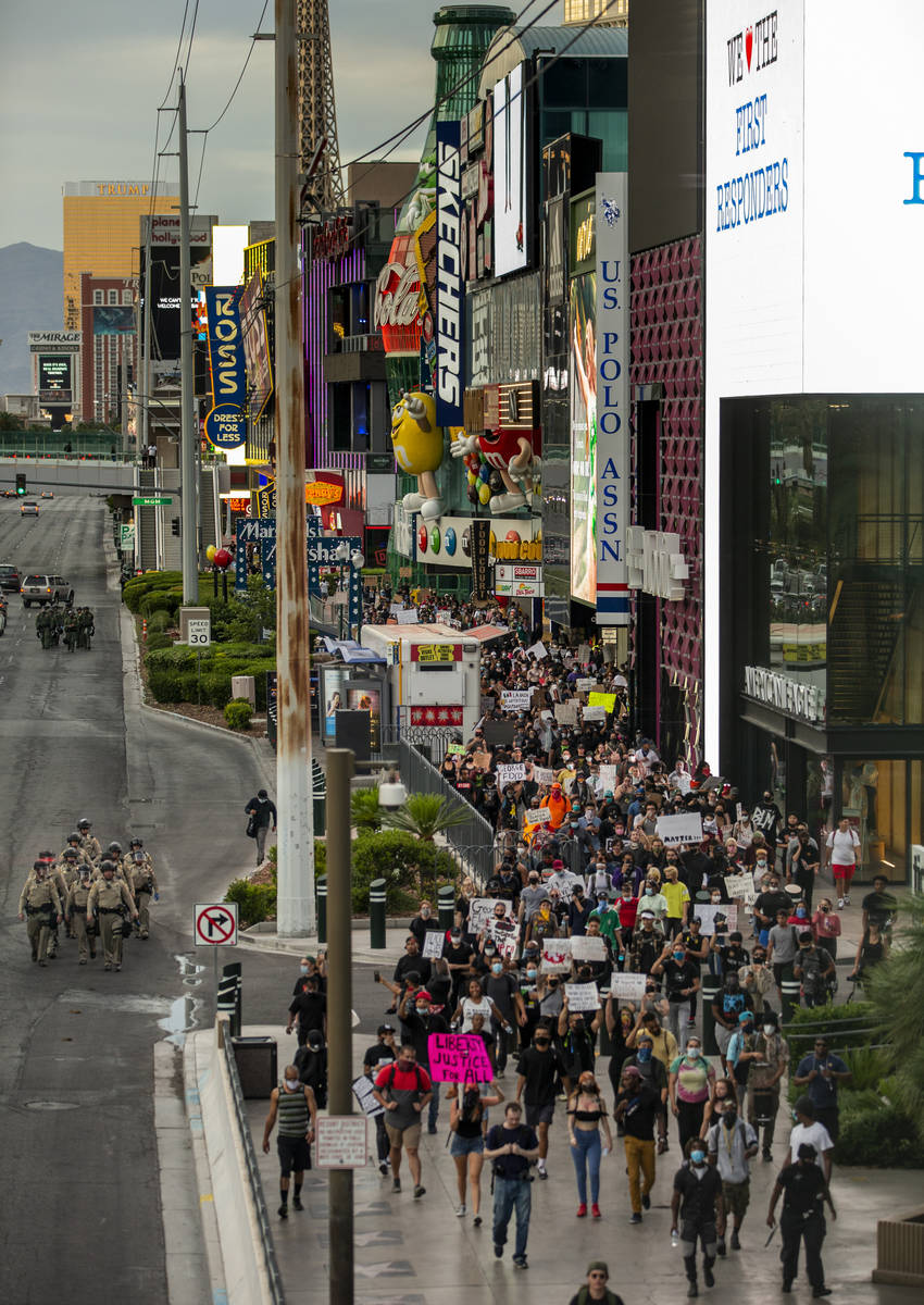 Las Vegas police officers and Black Lives Matter protesters walk along the Las Vegas Strip on S ...
