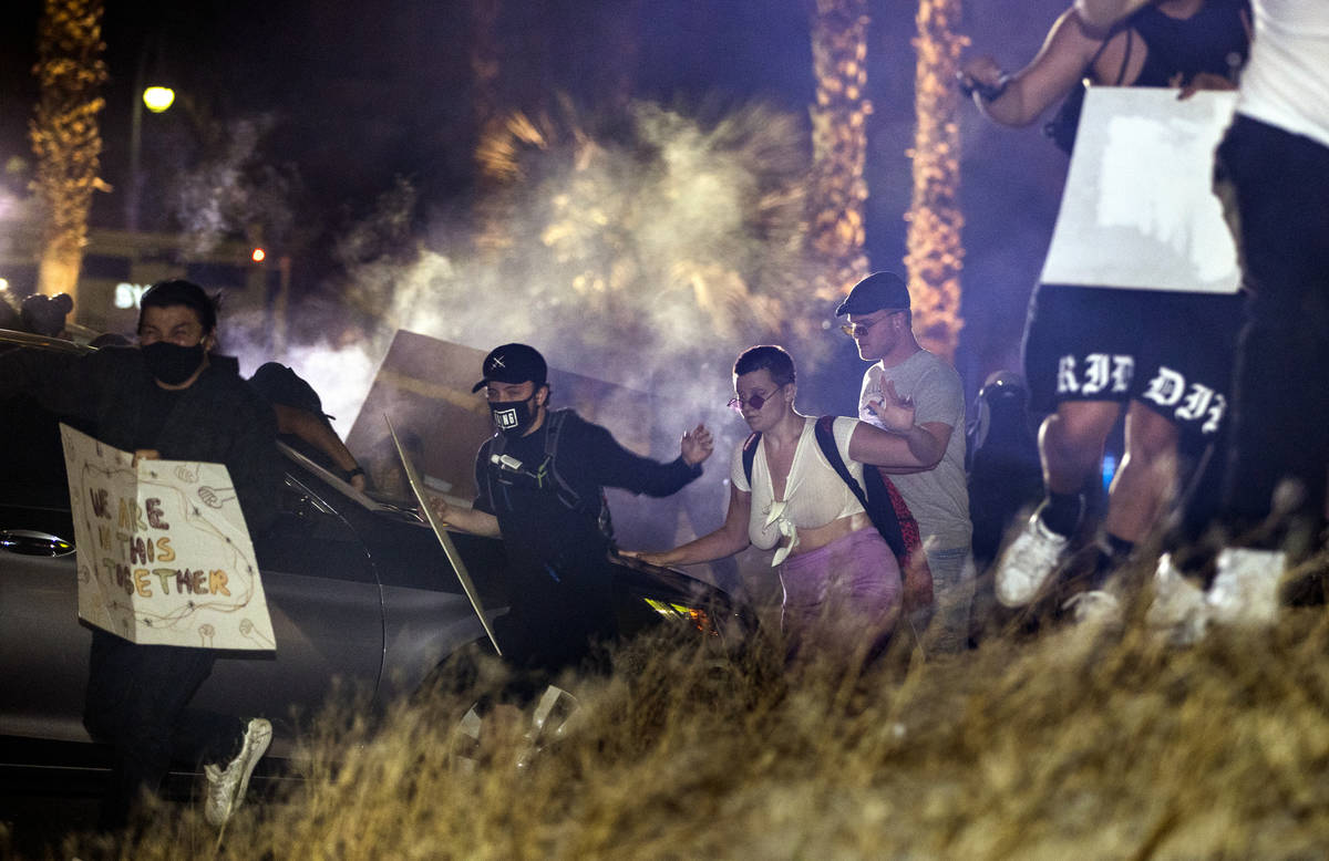 Protesters run after Las Vegas police fire tear gas and pepper bullets during a Black Lives Mat ...
