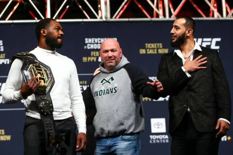 UFC President Dana White, center, looks on as Jon Jones, left, and Dominick Reyes face off duri ...