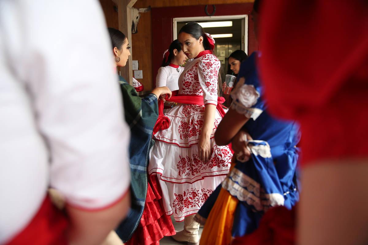 Linsy Enriquez, 16, left, assists Alondra Colon, 23, with her ensemble before a performance. Ev ...