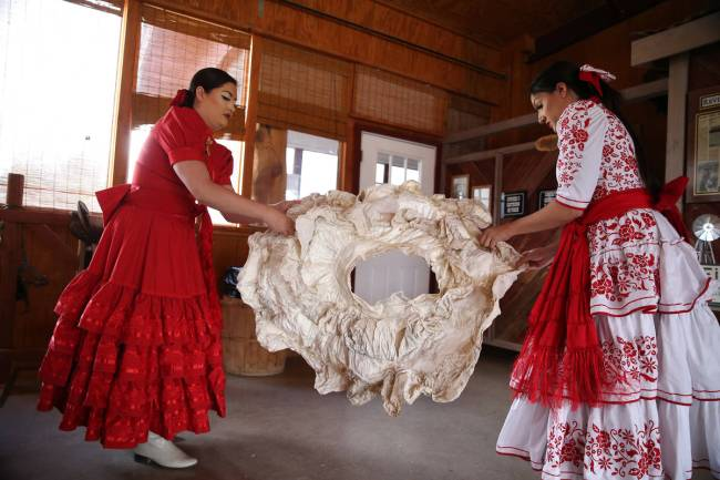 Viridiana, left, and her sister Alondra Colon, shape a crinoline to hold out their dresses befo ...