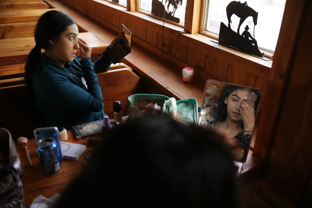 Linsy Enriquez, 16, left, and Melany Ortiz, 18, work on their make up as they prepare to perfor ...