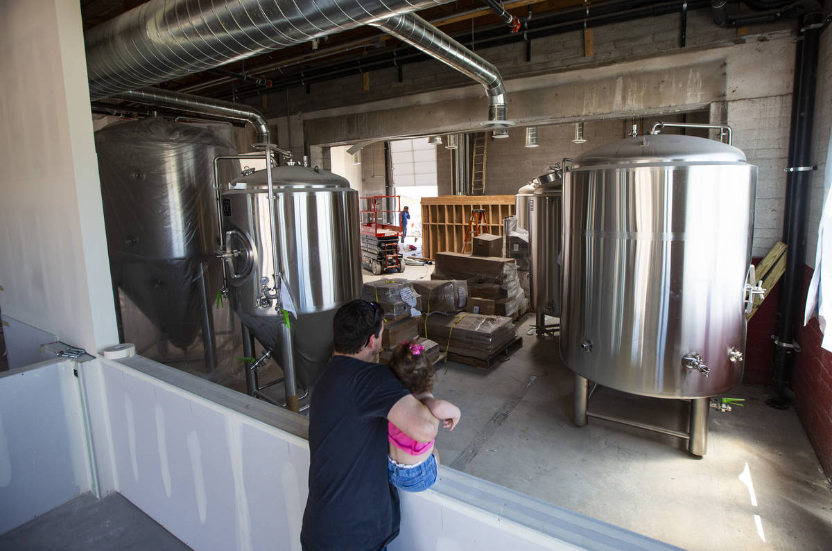 Jason Taylor, with daughter Ariana, 3, looks over work done at Nevada Brew Works during constru ...