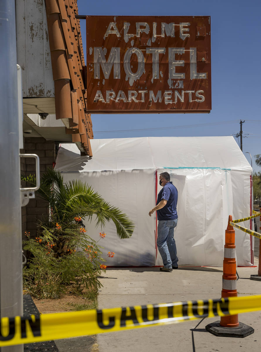 A crew leader from Earth Resource Group Environmental Services enters a white plastic tent cove ...