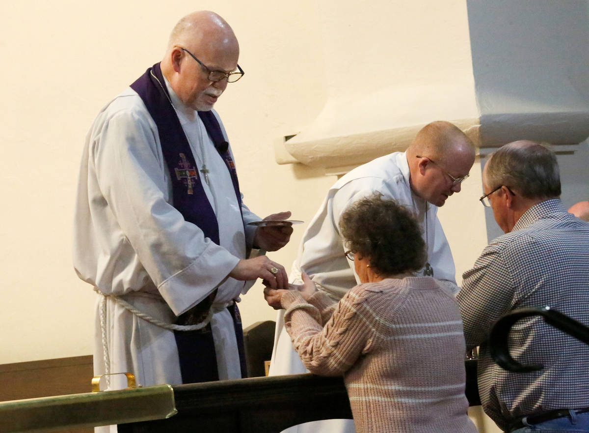 The Rev. J. Barry Vaughn, left and John Leslie Jr., a sub deacon, give the Holy Communion to fa ...