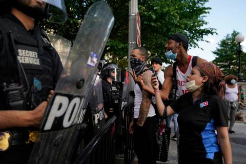 Demonstrators vent to police in riot gear as they protest the death of George Floyd, Saturday, ...