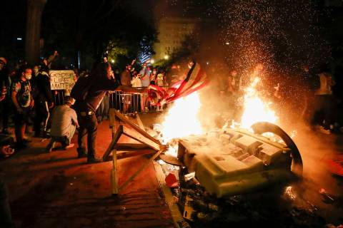 Demonstrators start a fire as they protest the death of George Floyd, Sunday, May 31, 2020, nea ...