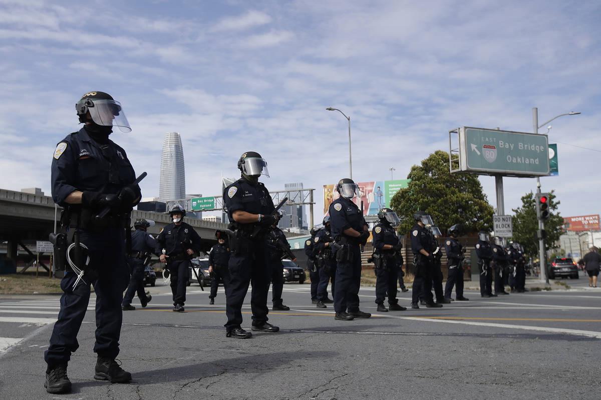 Police officers block a street near the San Francisco-Oakland Bay Bridge in San Francisco, Sund ...