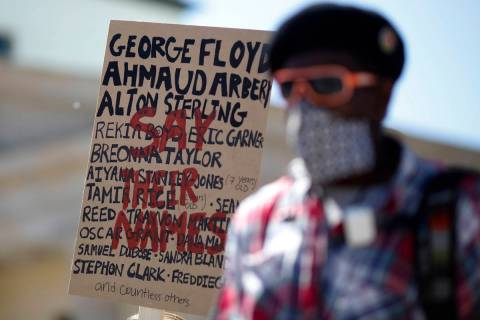 Ismael Kamara stand in front of a poster with names from people died after police violence the ...
