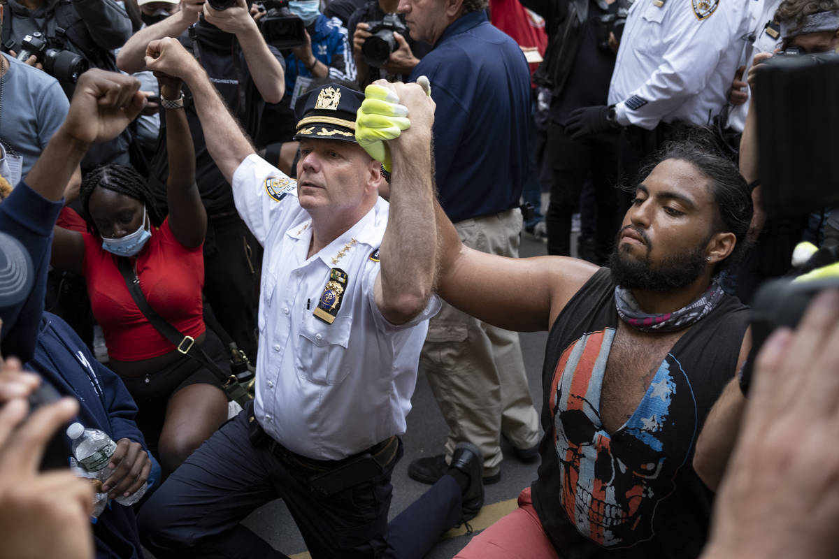 Chief of Department of the New York City Police, Terence Monahan, takes a knee with activists a ...