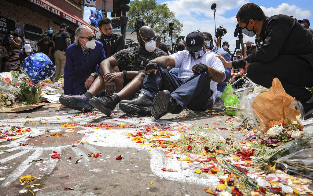 An emotional Terrence Floyd, second from right, is comforted as he sits at the spot at the inte ...