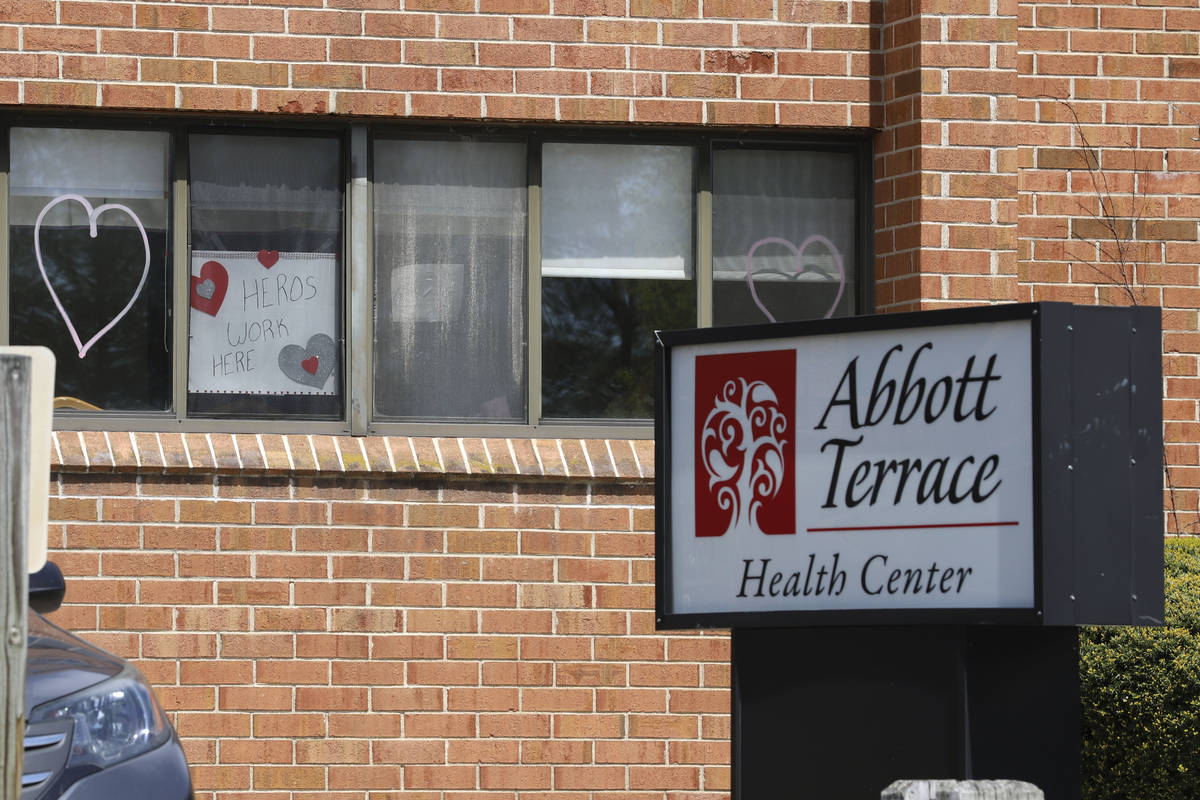 A sign for nursing home employees hangs in a window at the Abbott Terrace Health Center, Thursd ...