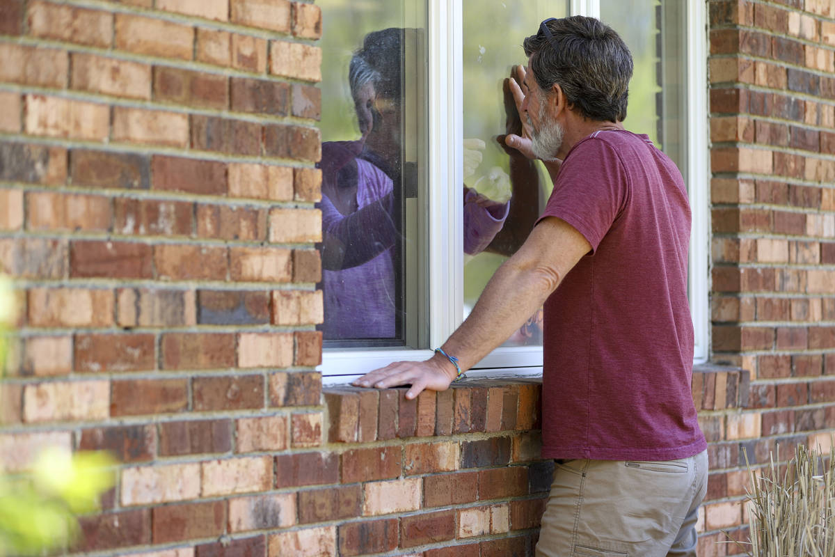 Jack Campise talks with his mother, Beverly Kearns, through her apartment window at the Kimberl ...