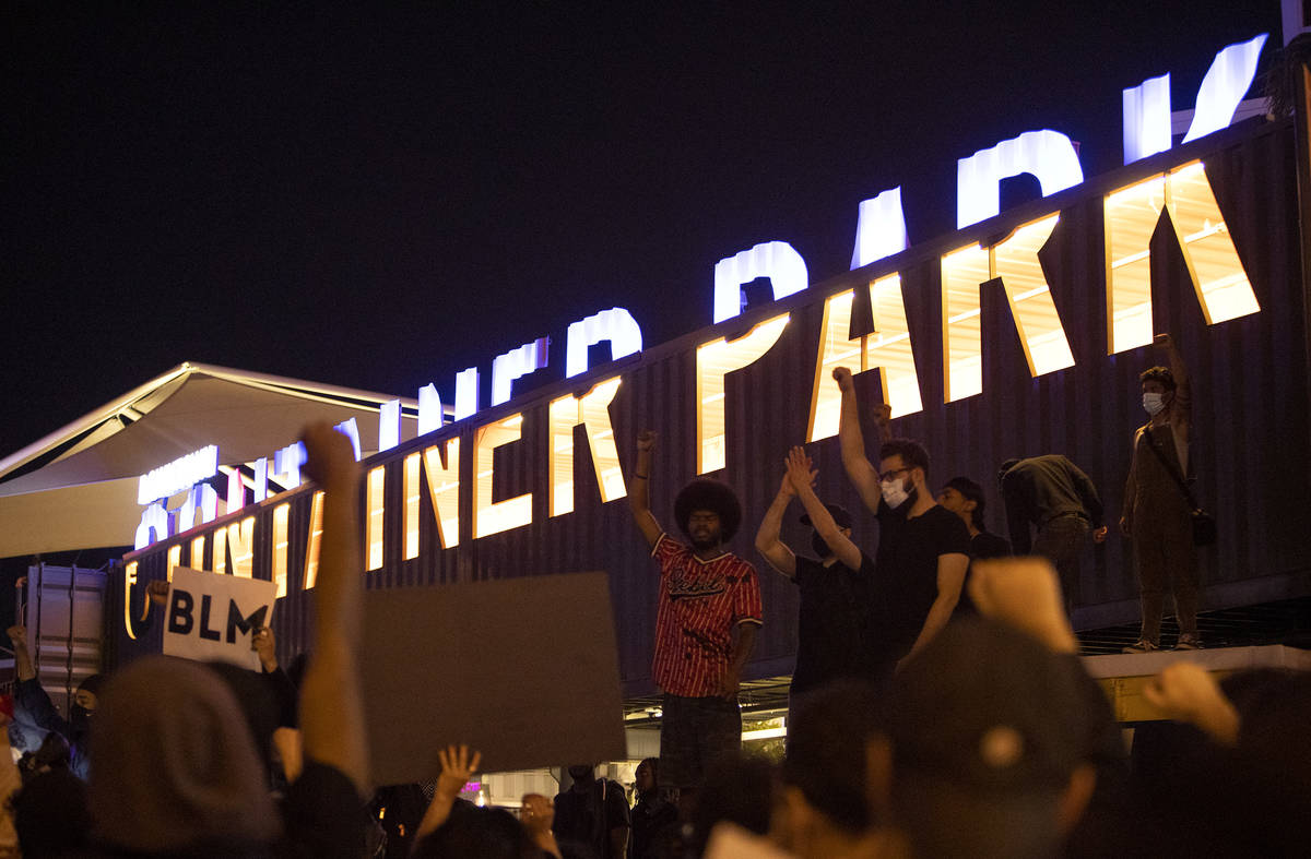 Black Lives Matter protesters take a knee and shout for George Floyd in Downtown Container Park ...