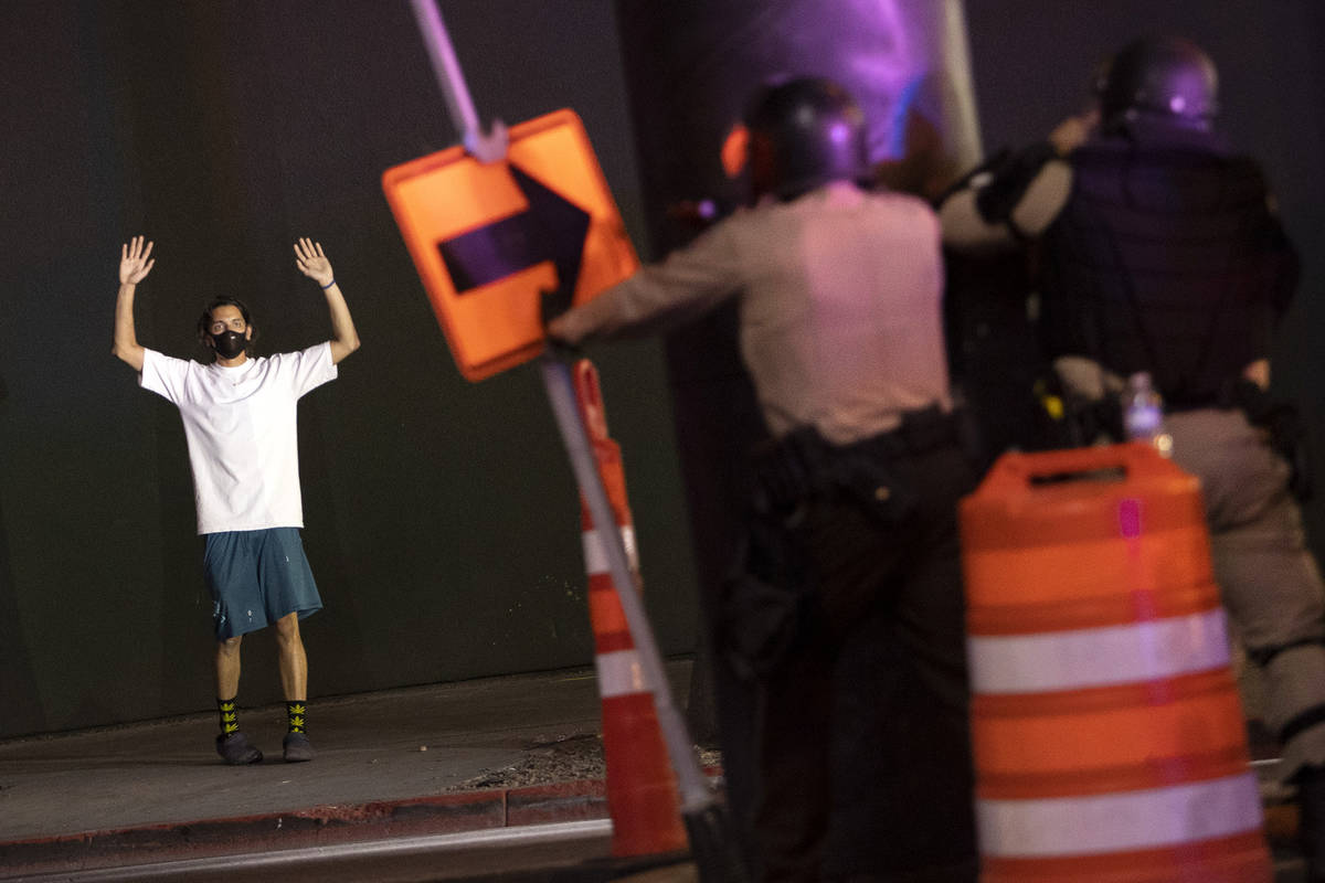 One protester puts his hands up while standing on the sidewalk as police officers ready to fire ...