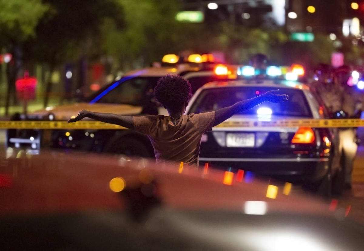 A woman walks towards police with her hands in the air after learning a protester was shot and ...