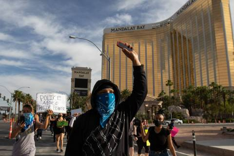A demonstrator raises his hand during a Black Lives Matter protest along the Las Vegas Strip on ...