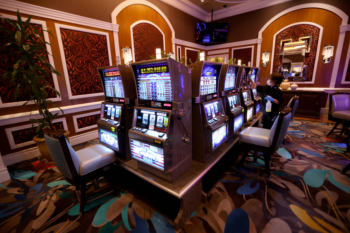 A worker cleans slot machines in the high limit room during a Bellagio media a tour showing &qu ...