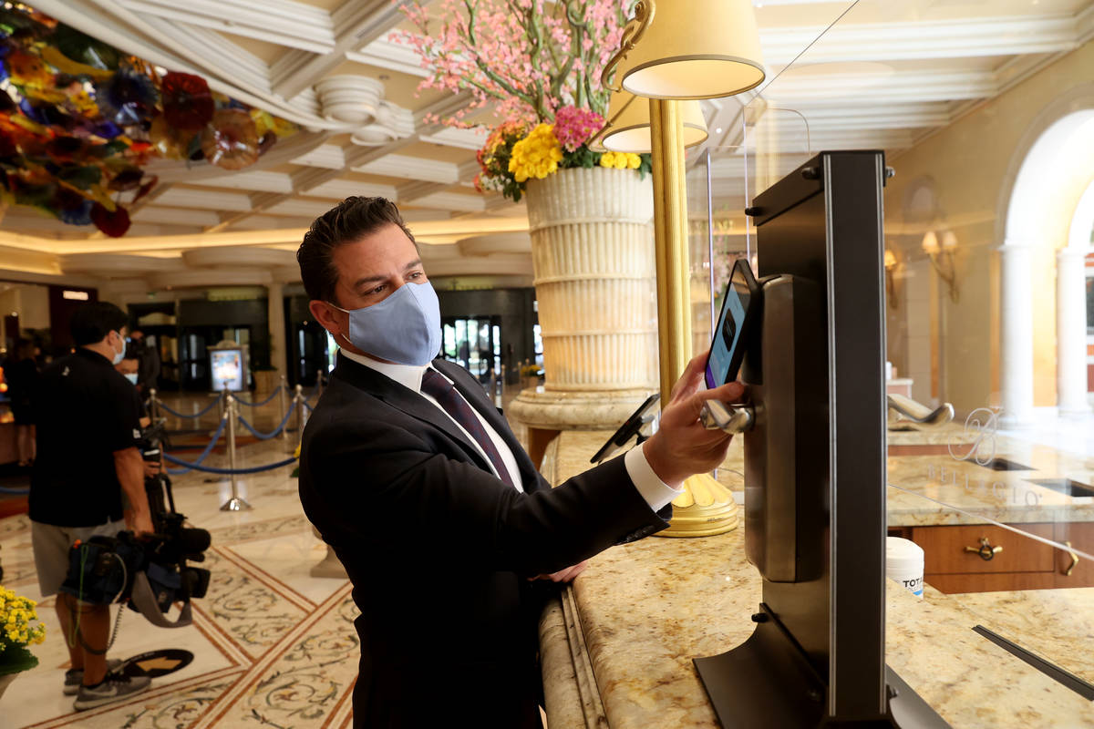 Andy Meese, MGM Resorts vice president of hotel operations, shows how to use a mobile device as ...