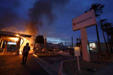 A man looks on as a bank burns after a protest over the death of George Floyd. (AP Photo/Gregor ...