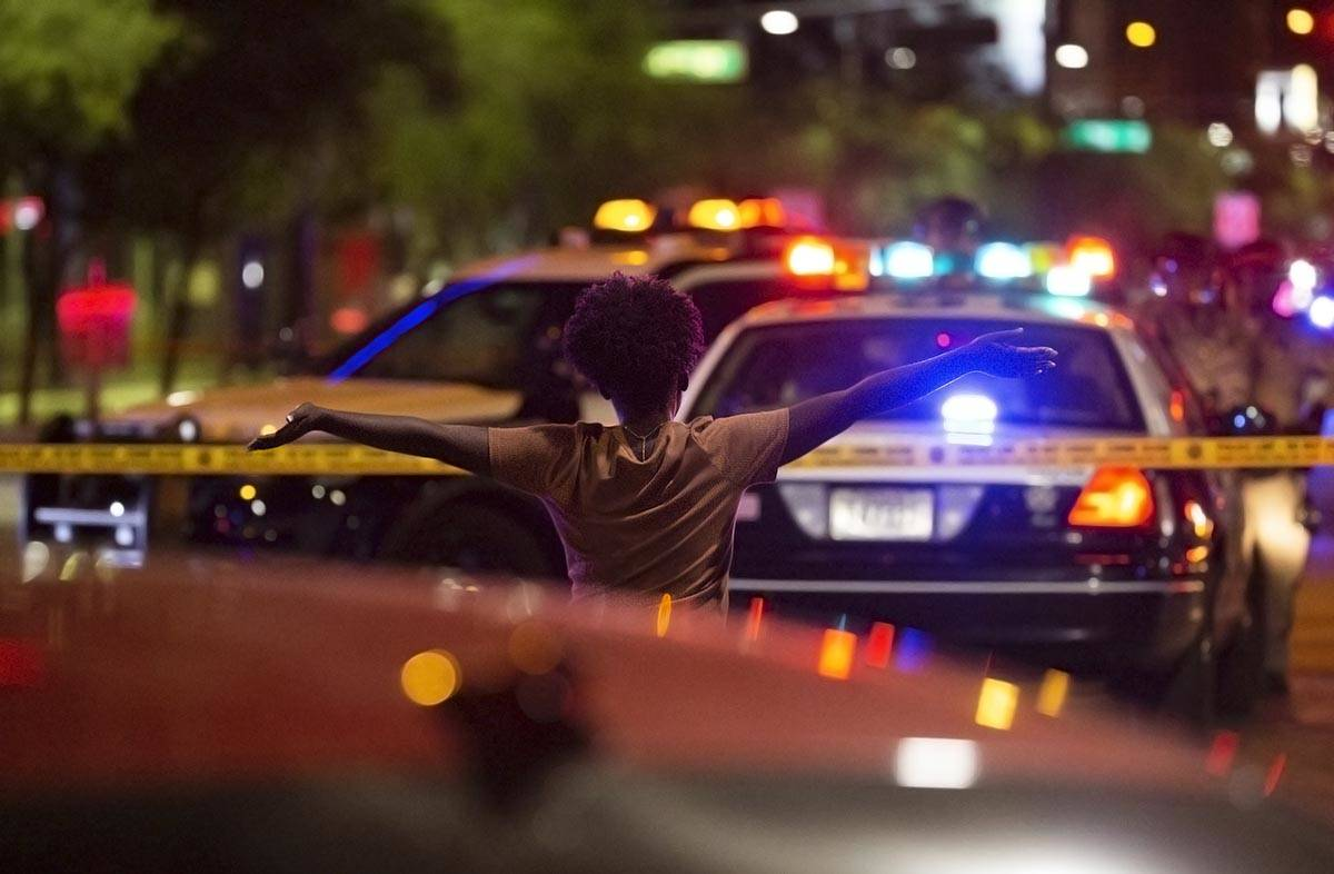 A woman walks toward police with her hands in the air after learning that a protester was shot ...