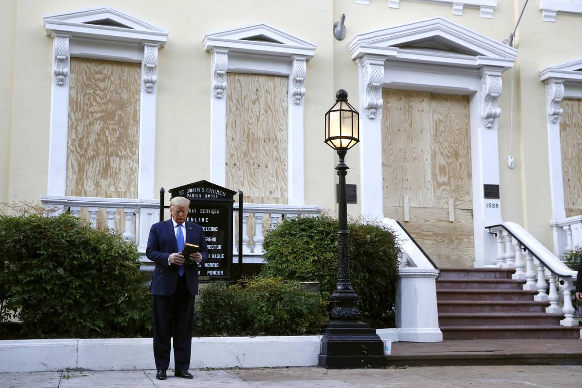 President Donald Trump holds a Bible as he visits outside St. John's Church across Lafayette Pa ...