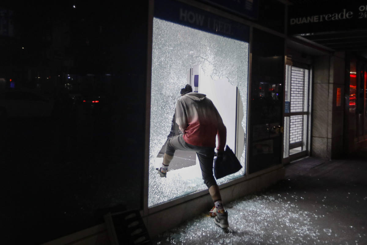 A person enters a store through a broken window Monday, June 1, 2020, in New York. (AP Photo/Fr ...