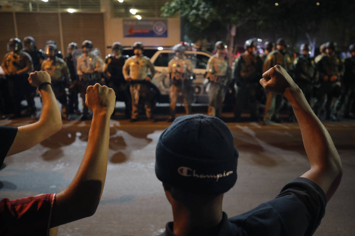 Protesters raise their fists during a rally Monday, June 1, 2020, in Las Vegas, over the death ...