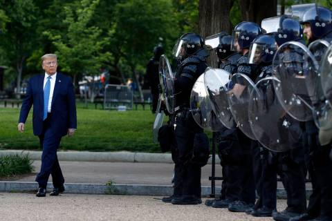President Donald Trump walks past police in Lafayette Park after he visited outside St. John's ...