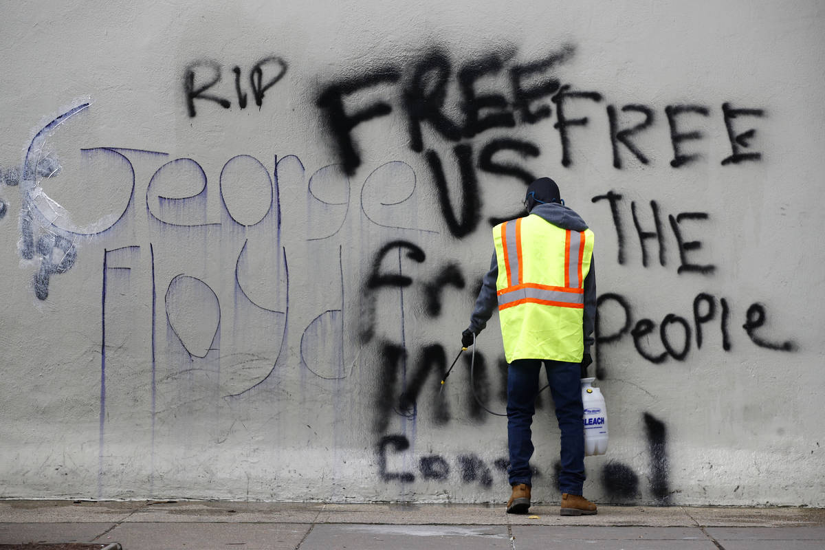 A worker removes graffiti from a building, Tuesday, June 2, 2020, in Washington, following prot ...